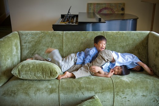 Stock Photo: 4033-469 Three boys playing on a couch