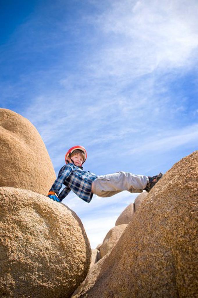 Boy straddling boulders, Joshua Tree National Monument, California, USA : Stock Photo