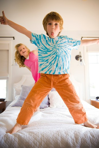 Boy playing on the bed with his sister : Stock Photo