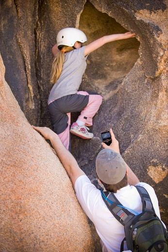 Stock Photo: 4033-476 Girl rock climbing being filmed by her father, Joshua Tree National Monument, California, USA