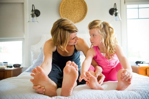 Young woman sitting with her daughter on the bed : Stock Photo