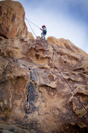 Boy rock climbing, Joshua Tree National Monument, California, USA : Stock Photo