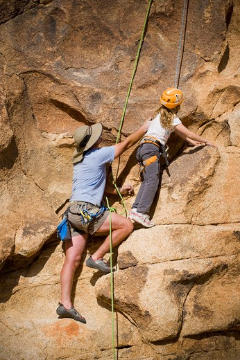 Mid adult man helping his daughter to climb a rock, Joshua Tree National Monument, California, USA : Stock Photo
