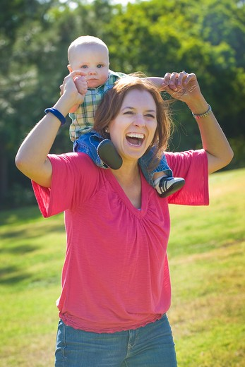 Young woman playing with her son in a park : Stock Photo