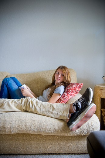 Teenage girl reading a book on a couch : Stock Photo