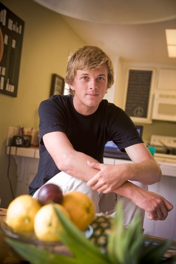 Teenage boy sitting in the kitchen : Stock Photo