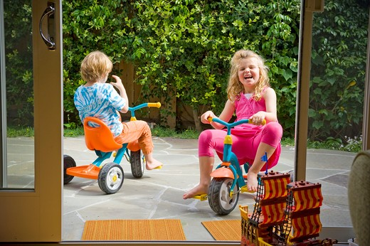 Stock Photo: 4033-496 Boy and his sister riding tricycles