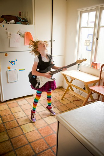 Stock Photo: 4033-502A Girl playing an electric guitar in a kitchen