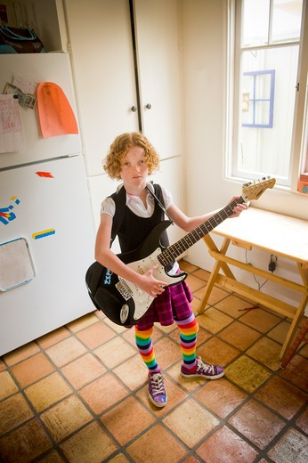 Girl playing an electric guitar in a kitchen : Stock Photo