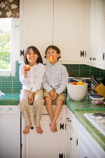 Boy and his sister sitting on a kitchen counter and eating apples : Stock Photo