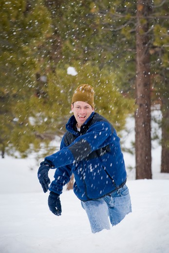 Mid adult man throwing snowballs : Stock Photo