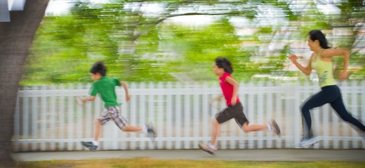 Stock Photo: 4033-511A Mid adult woman running with her children in a park