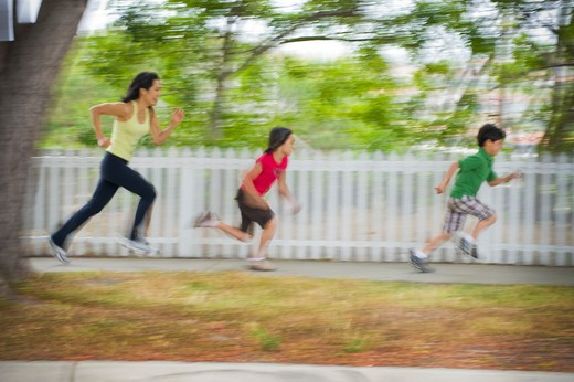 Stock Photo: 4033-511B Mid adult woman running with her children in a park