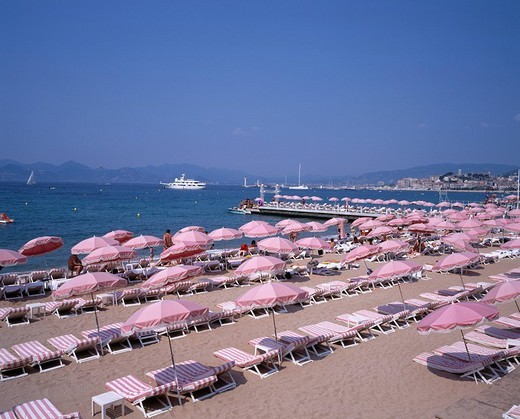 It is as a Croisette along. Beach side Cannes Cote d´Azur France Sea Parasol Beach bed Sandy beach Sea Ship : Stock Photo