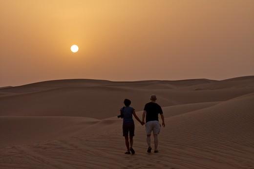 Stock Photo: 4038-223 Couple in the desert at sunset, Dubai, United Arab Emirates