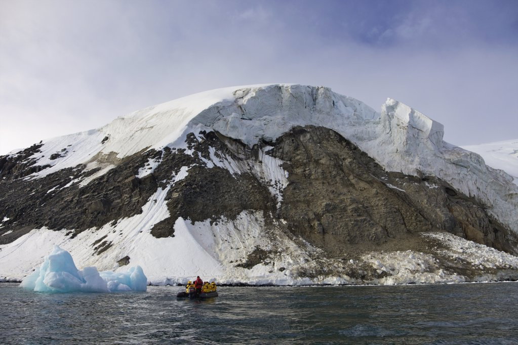 Tourists in zodiac inflatable near Alkefjellet cliffs, Spitsbergen, Svalbard Islands, Norway : Stock Photo