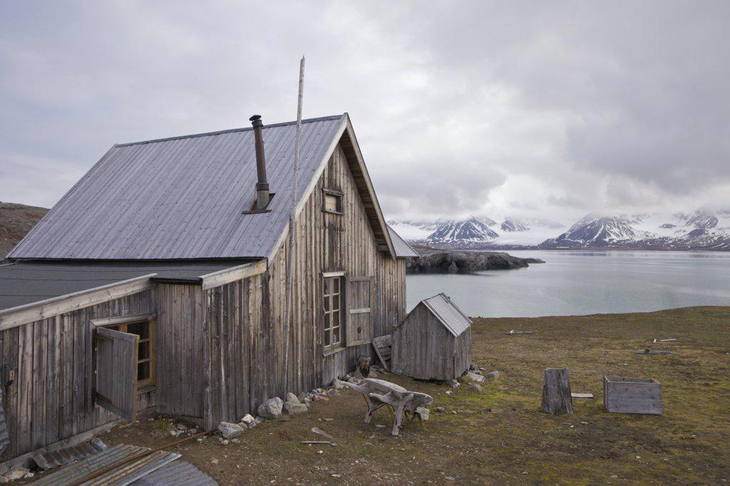 Old wooden trapper's hut on the coast, Camp Mansfield, Blomstrandhalvoya, Spitsbergen, Svalbard Islands, Norway : Stock Photo