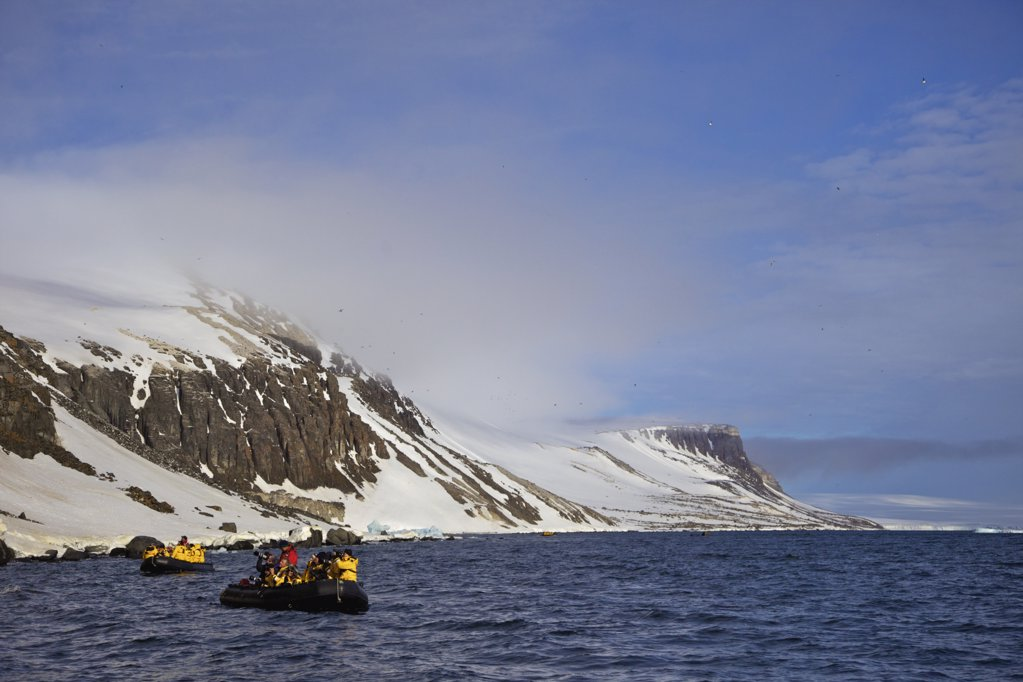 Stock Photo: 4042-1104 Tourists in zodiac inflatable near Alkefjellet cliffs, Spitsbergen, Svalbard Islands, Norway