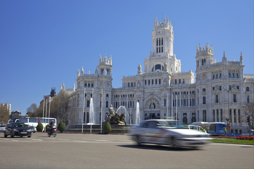 Traffic at a town square with a palace, Palacio De Comunicaciones, Plaza De Cibeles, Madrid, Spain : Stock Photo