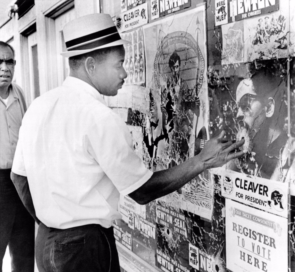 Stock Photo: 4048-10032 An African American pokes his finger into a bullet hole in the Oakland Black Panther's headquarters. Two Oakland police officers allegedly fired over a dozen shots into the building. There were no injuries. Sept. 10, 1968.