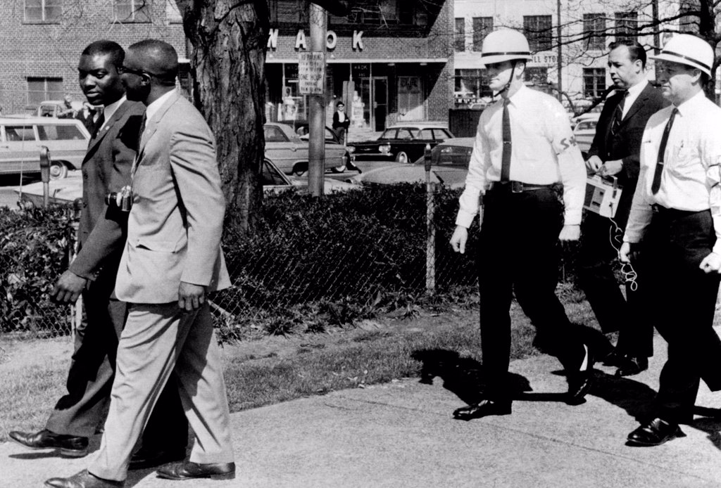 Stock Photo: 4048-10043 A Ku Klux Klan 'Security Patrol' walk behind Jeremiah X (left in light suit), leader of Atlanta's Black Muslim sect. Jeremiah X and an aide, were turned away when they attempted to tour downtown Hurt Park where Klan was having rally. March 22, 1964.