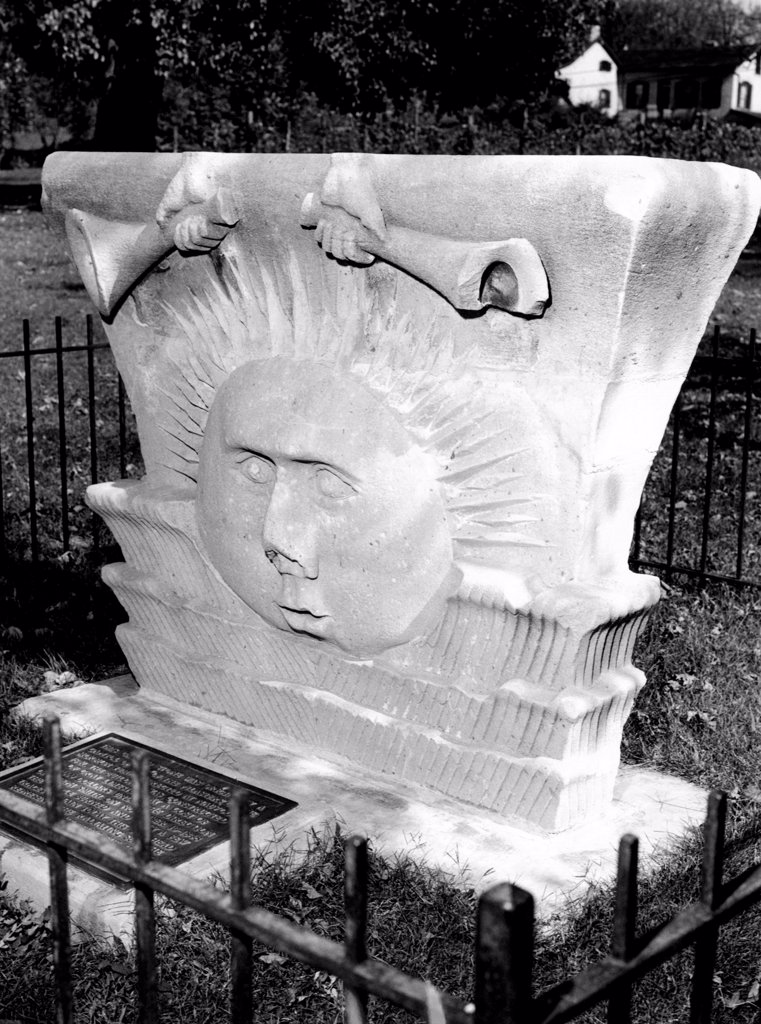 Stock Photo: 4048-10111 Surviving sunstone at the reconstructed Mormon Temple at Nauvoo, Illinois. It depicts sun face emerging between clouds beneath a pair of hand-held trumpets. They are believed to be inspired by Paul's writing in 1 Corinthians 15:40-42 which likened the glory of the heavenly kingdoms to that of the sun, the moon and the stars. The stone was carved in the 1840s.