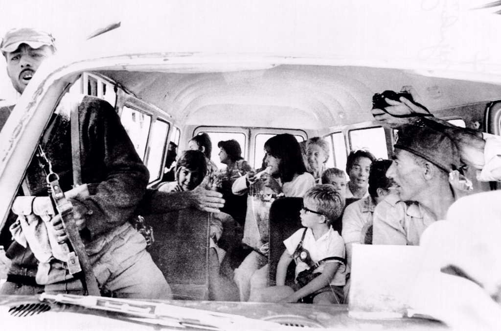 Women and children hostages about to be freed by the airline hijackers. They are arriving at the Intercontinental Hotel in Amman, Jordan. The hijacker with an automatic gun attempts to clear the road of newsmen as a photographer sticks his camera into the van. Sept. 12, 1970. : Stock Photo