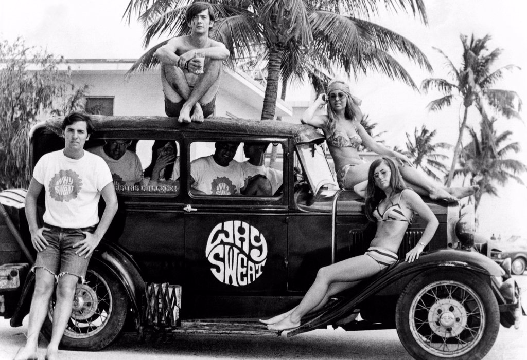 Students who made the spring break scene at Ft. Lauderdale pose with a 1930s roadster with a 'Why Sweat' emblem. April 20, 1968. : Stock Photo
