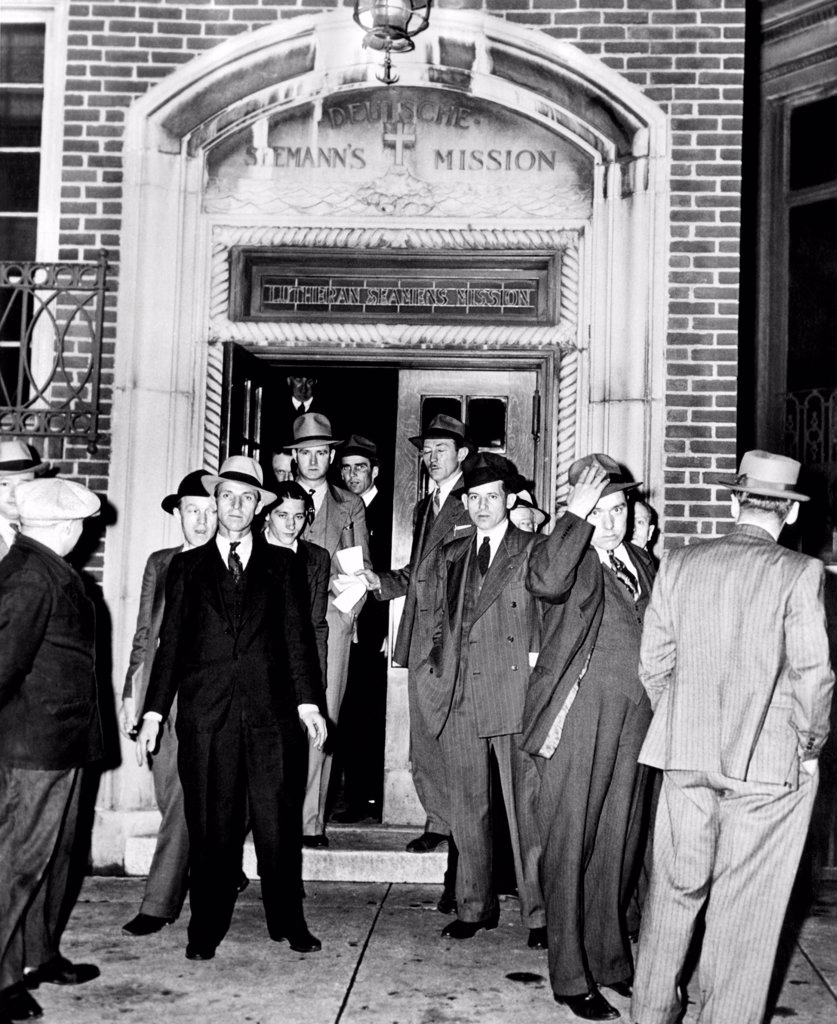 Stock Photo: 4048-10191 German aliens leaving the Deutsche Seaman Mission on Hudson Street for Ellis island in the custody of U.S. Immigration Service agents. They were unable to work for their employers after war broke out in Europe. May 7, 1941.