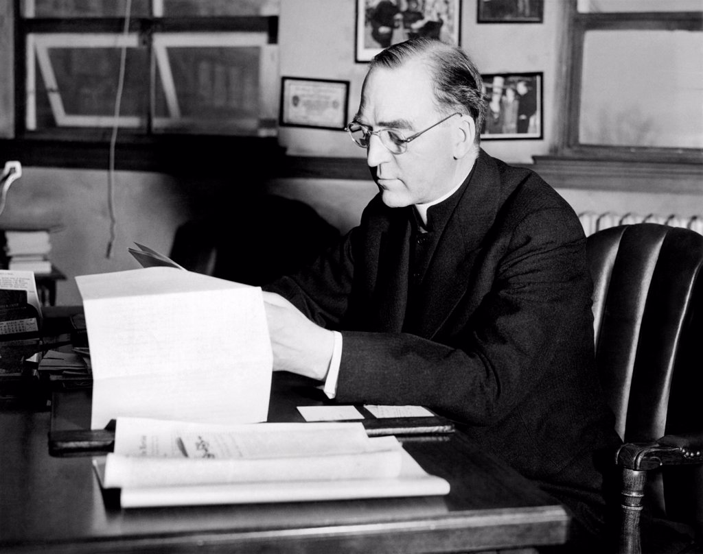 Father Edward J. Flanagan, founder and director of Father Flanagan's Boy's Home at Boys Town, Nebraska, is shown at his desk. Ca. 1935. : Stock Photo