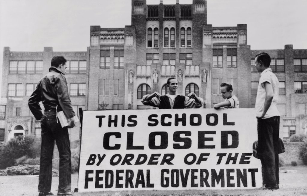 Stock Photo: 4048-10433 Little Rock Central High was closed to avoid integration. Four students pose with a large sign reading 'This school closed by order of the federal government.' The city government closed the school for the 1958-59 academic year rather than continue racial integration.