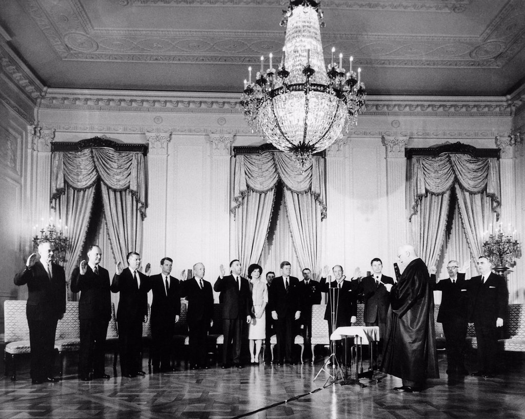 Stock Photo: 4048-10702 Swearing-In Ceremony of President Kennedy's Cabinet. Jan. 27, 1961. Chief Justice Earl Warren administers Oath to (L-R) Dean Rusk, Douglas Dillon, Robert McNamara, Robert F. Kennedy, J. Edward Day, Stewart Udall, Mrs. Kennedy, President Kennedy, Adlai Stevenson, Orville Freeman, hidden: Luther Hodges, Arthur Goldberg, Abraham Ribicoff. In rear: Gen. C.V. Clifton, Col. Godfrey McHugh, Cmdr. Tazewell Shepard. White House, East Room.