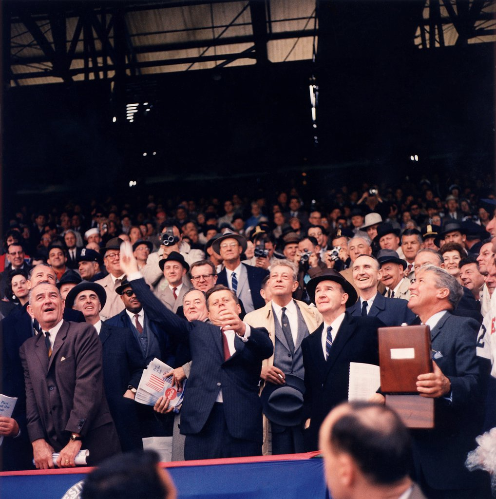 President Kennedy throws out first ball on Opening Day of 1961 Baseball Season. First row L-R: VP Johnson, Kennedy, Dave Powers, Elwood Quesada. Second Row: Abraham Ribicoff, Andrew Hatcher, Hubert Humphrey, Everett Dirksen, Mike Mansfield. Third row: Lawrence O'Brien. April 10, 1961. : Stock Photo