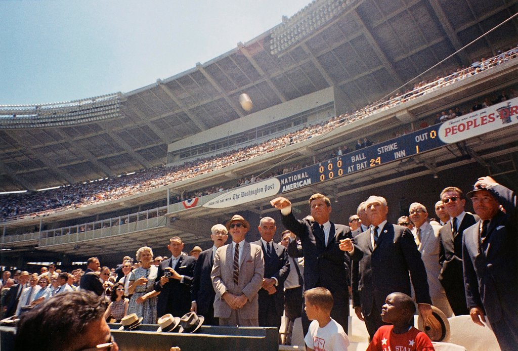 President Kennedy throws out first ball of the 32nd All-Star Baseball Game. Flanking the President, L-R: Speaker John McCormack, Dave Powers, VP Johnson, President Kennedy, Baseball Commissioner Ford Frick, Lawrence O'Brien. July 10, 1962. : Stock Photo