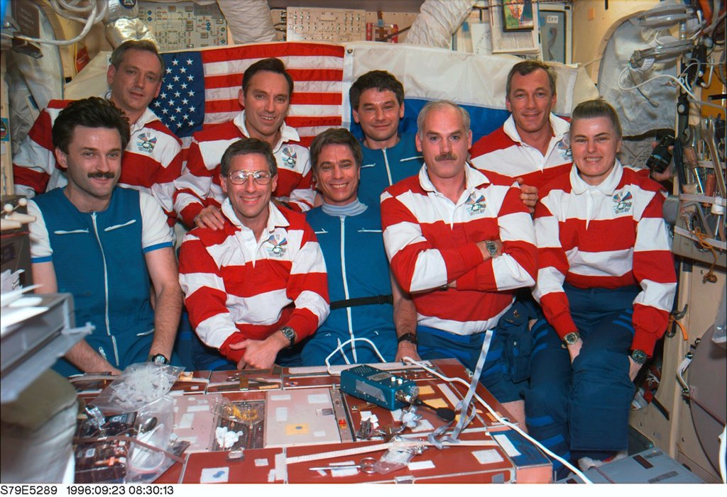 Stock Photo: 4048-10745 Astronauts and Cosmonauts aboard Russia's Mir Space Station. Russians are wearing blue, and Americans wearing red stripes. Front row, L-R: Aleksandr Kaleri, John Blaha, Jay Apt, William Readdy, and Shannon Lucid. Back row, L-R: Thomas Akers, Carl Walz, Valery Korzun, and Terrence Wilcutt.