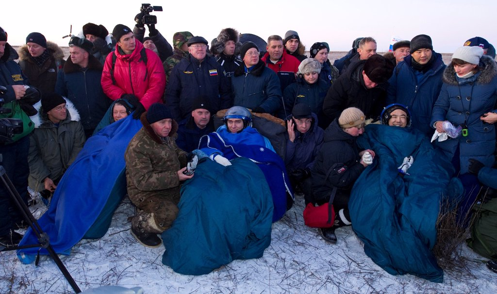 After five months in space, space travelers recline in chairs the Soyuz TMA-02M capsule after they landed in Kazakhstan. The International Space Station Expedition 29 crew, L-R: Mike Fossum (USA), Sergei Volkov(Russia), and Satoshi Furukawa (Japan). Nov. 21, 2011. : Stock Photo