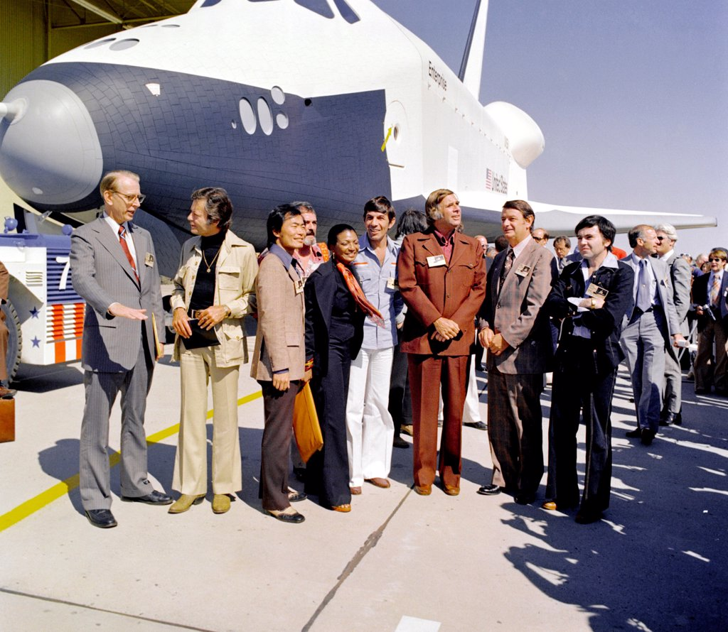 Stock Photo: 4048-10834 Star Trek television cast members at the roll out of the Space shuttle prototype Enterprise. L-R: James Fletcher, NASA Administrator, DeForest Kelley (McCoy), George Takei (Sulu), James Doohan (Scott), Michelle Nichols (Lt. Uhura), Leonard Nimoy (Spock), Gene Rodenberry, and Walter Koenig (Chekov). Sept. 17, 1976.