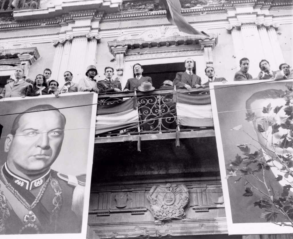 Stock Photo: 4048-10888 Bolivian political celebration. The Bolivian cabinet awaits the arrival of President Victor Paz Estenssoro. The balcony is decorated with giant photos of former president Gualberto Villarroel López (left) and Paz Estenssoro. 1952.