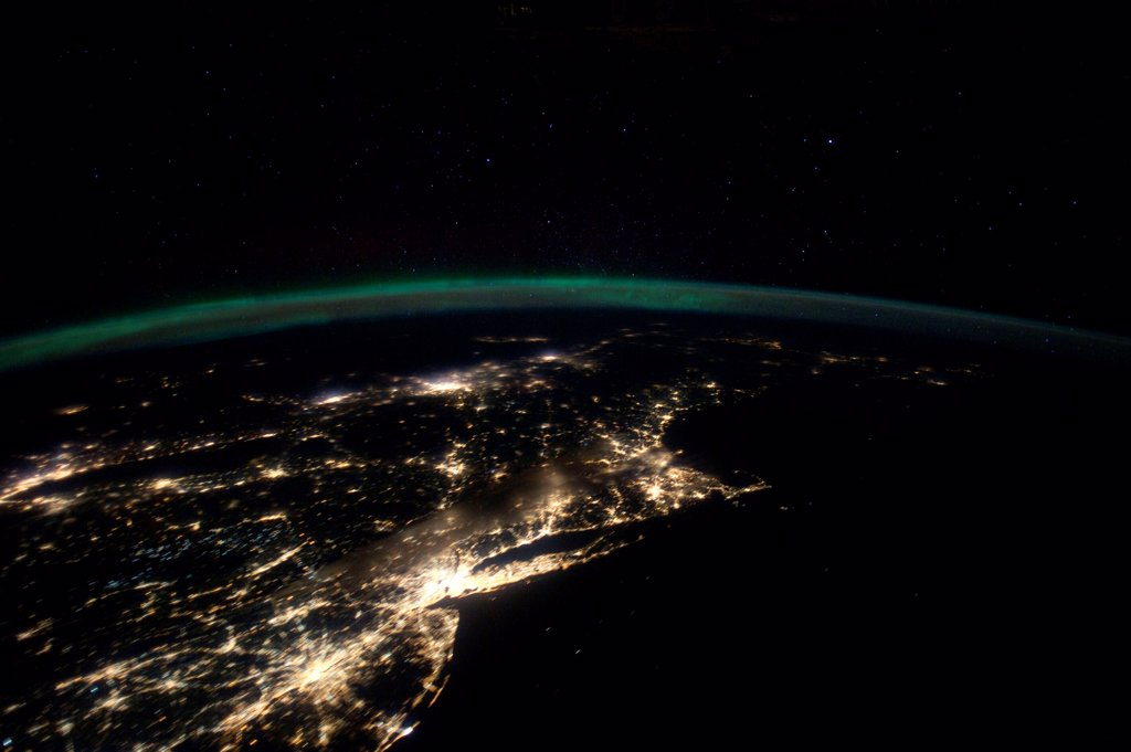 Night lights from the Philadelphia-New York City-Boston corridor. At left is western Lake Ontario shoreline with Toronto , Montreal is at near center.  The atmospheric limb and light activity from Aurora Borealis appear intertwined. Jan. 29, 2012. : Stock Photo