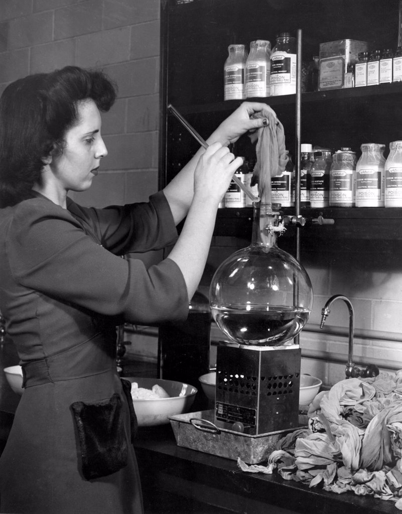 DuPONT COMPANY LABORATORY--Woman starting a pair of used nylons through a process developed at the laboratory which chemically unravels the stockings all the way back to their original complex components.(1940's) : Stock Photo