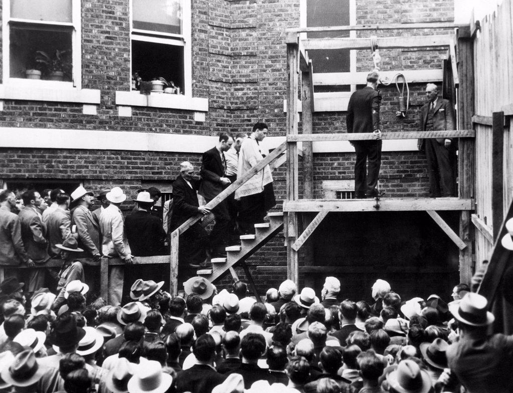 Stock Photo: 4048-1418 Roscoe 'Red' Jackson (behind priest) walks up the steps before he is hanged. He was convicted of killing a travelling salesman who gave him a ride. Galena, Missouri, 1937