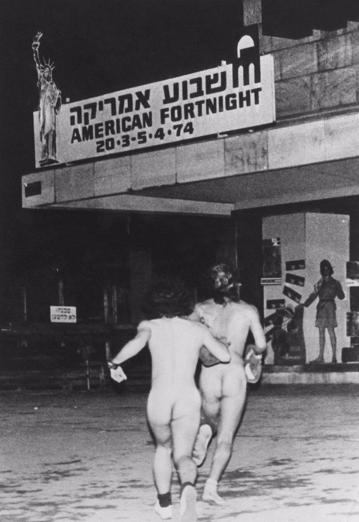 Two Israeli streakers running through downtown Tel Aviv, Israel, 1974. : Stock Photo