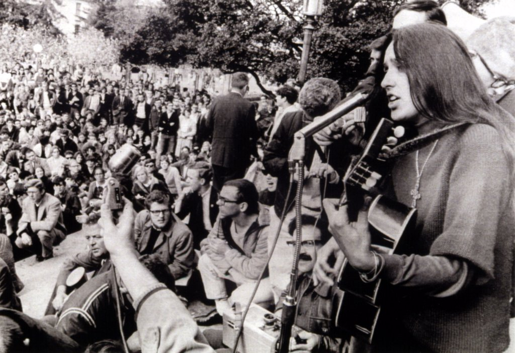 12-2-64 BERKELEY, CALIf.: Folk singer Joan Baez strums her guitar and sings freedom songs during a sit-in at the University of California at Berkeley. : Stock Photo