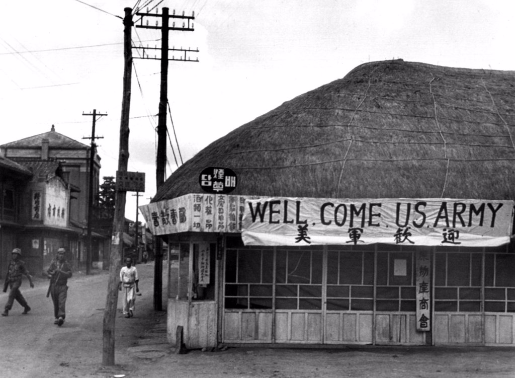 Stock Photo: 4048-1580 7/8/50--SUWON, KOREA: A tea shop in Suwon put up a large sign to welcome US troops during the war.