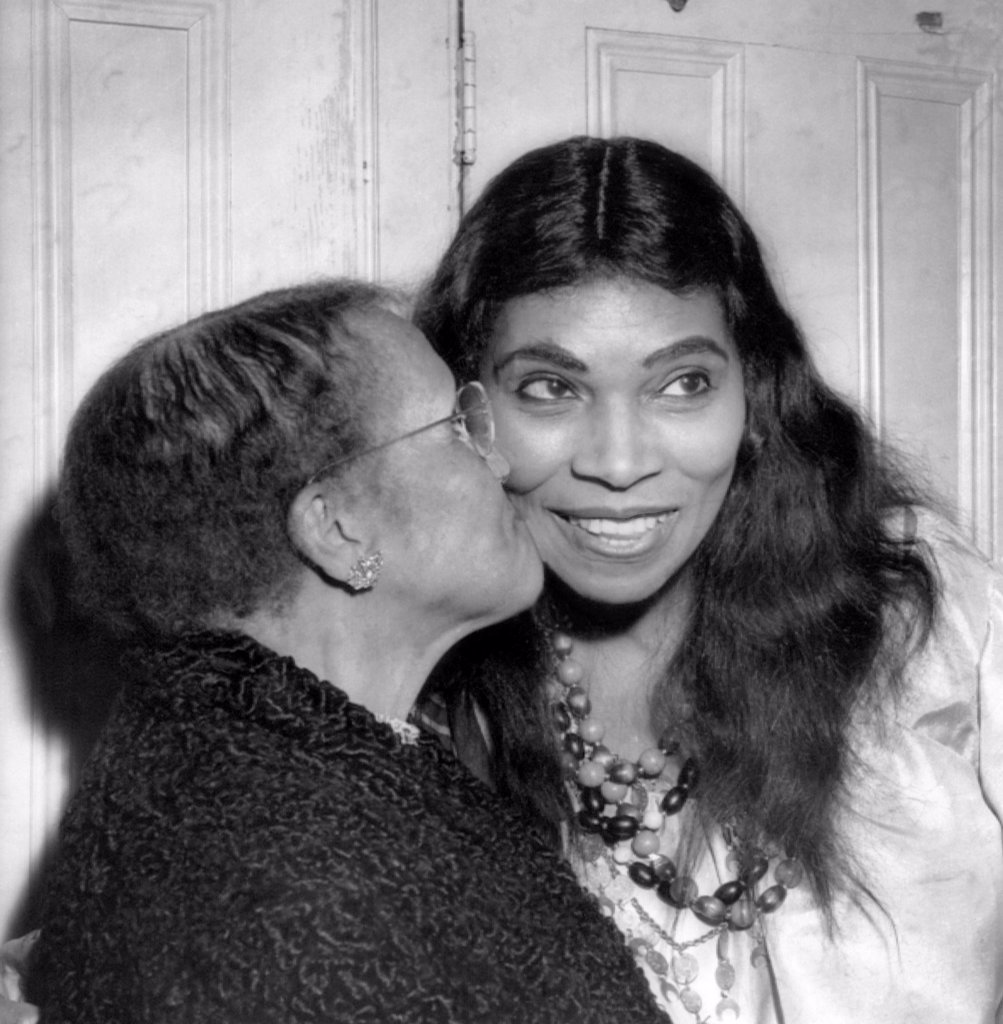 Anna Anderson kisses her daughter, singer Marian Anderson, after a performance of Verdi's 'The Masked Ball' at the Metropolitan Opera, 1955 : Stock Photo