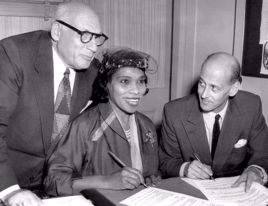 Stock Photo: 4048-1638 Singer Marian Anderson signs a contract with Metropolitan Opera representative Rudolf Bing (right). She was the first black performer to sing leading roles for the Met. Her manager, Sol Hurok (left), looks on, 1954