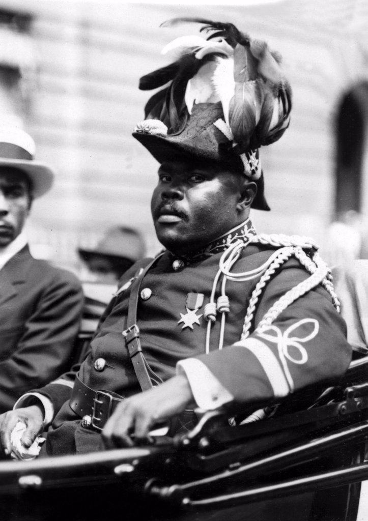 Marcus Garvey, the Negro Moses, rides through the streets of Harlem, New York City, amid delegates resplendent in plummage and golden braid.  August 1922. : Stock Photo