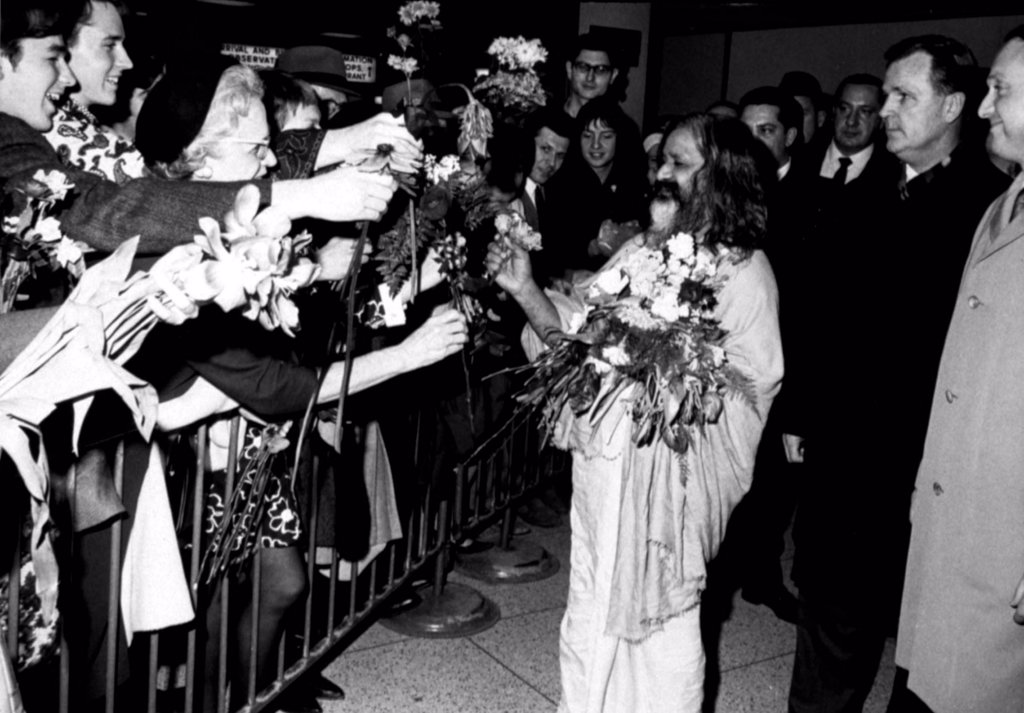Stock Photo: 4048-1657 MAHARISHI MAHESH YOGI, head of the spiritual regeneration movement, accepts flowers from his followers, greeting his arrival at a NY airport,  January 18, 1968
