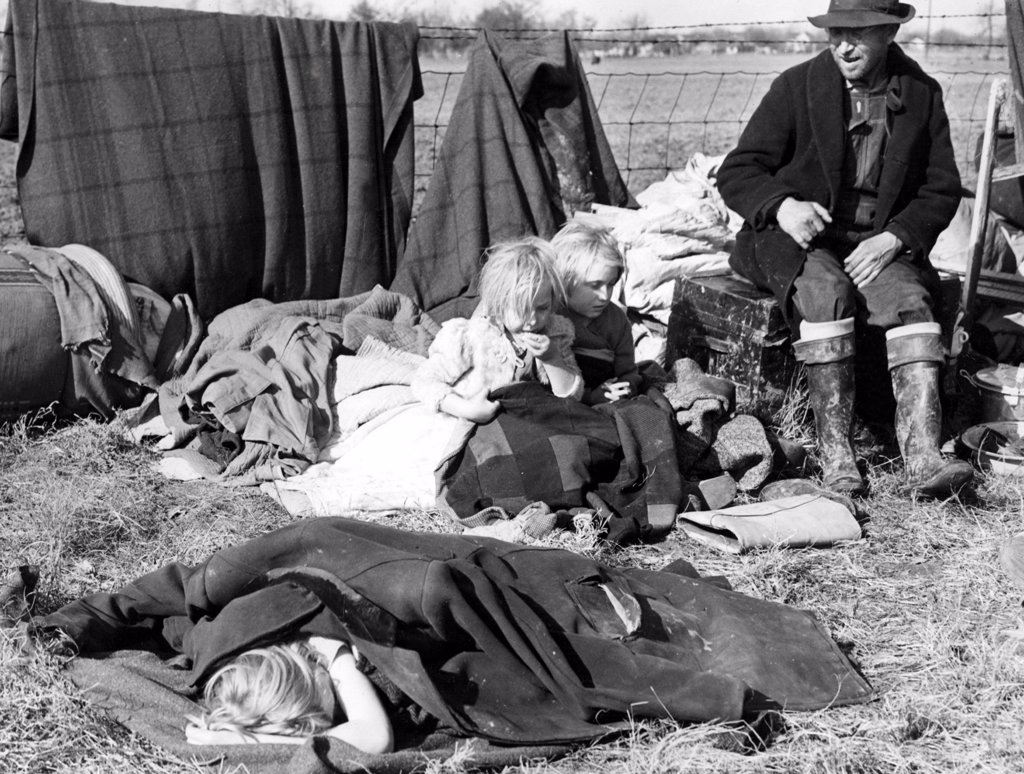 Stock Photo: 4048-1863 SIKESTON, MO--Evicted from their home, a sharecropper and his three little children sit amonst their meager possessions on the edge of a state highway and wait, along with a thousand other evicted croppers, for aid from the government.  January 11, 1939.