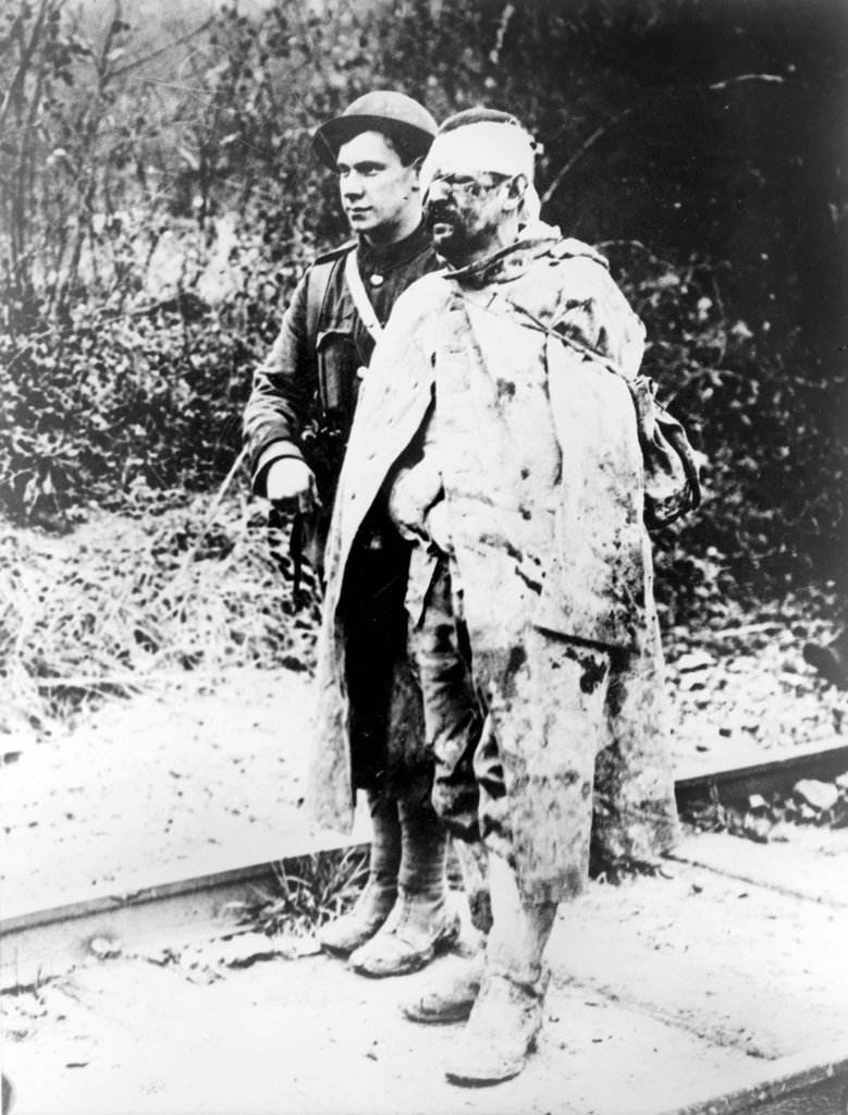 Stock Photo: 4048-2334 World War I, Another sort of war ruin - after several days in the trenches, a British Red Cross orderly escorting a wounded, captured German soldier to a field hospital for treatment, 1914-1918.